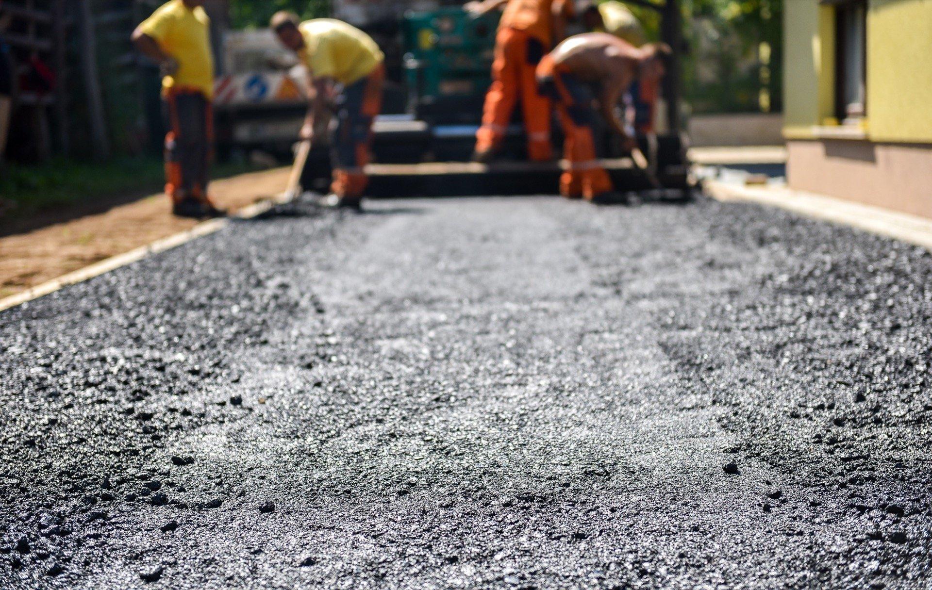 Workers building asphalt driveway